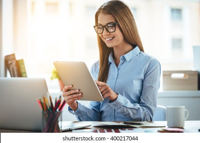 Lets check my timetable! Cheerful young beautiful woman in glasses using her touchpad with smile while sitting at her working place