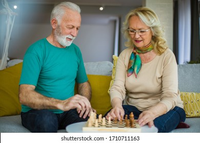 Let's compare knowledge. Seniors couple plying chess at home.