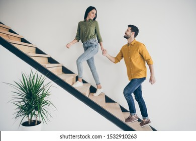 Let's explore this place! Full size profile photo of handsome guy and his pretty lady walking to bedroom go up stairs in just bought modern flat indoors wear casual clothes