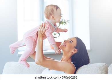Lets fly! Cheerful beautiful young woman holding baby girl in her hands and looking at her with love while sitting on the couch at home