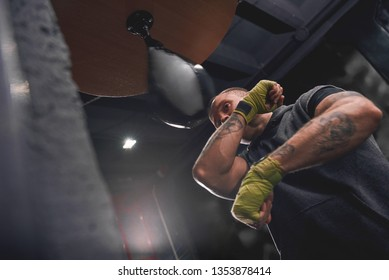 Let's get ready to rumble. Arm workout, professional young boxer with green hands wraps hitting punching speed bag in boxing gym