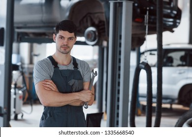 Let's get it started. Portrait of serious worker in uniform that stands in his workshop with wrench in hand.