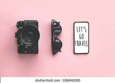 Let's go Travel text on stylish black smartphone  screen,sunglasses, photo camera on pink background. stylish summer vacation flat lay. time to travel