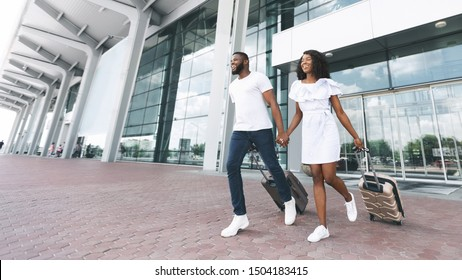 Let's go to trip! Happy african american couple running with luggage at airport exterior, panorama, empty space