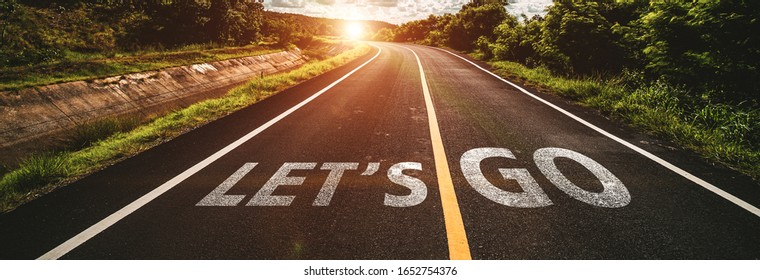let's go written on highway road in the middle of empty asphalt road at  beautiful blue sky.