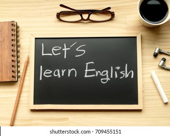 let's learn English - text on the blackboard to invite people to learn English with the background of work space, coffee, glasses, earphone, pencil and book