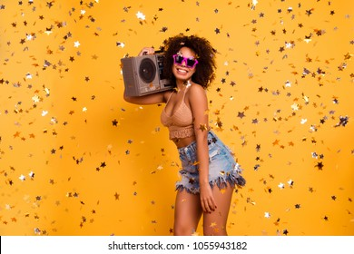 Let's make some noise! I'm club bunny! Careless fancy wild african female company-keeper is dressed in summer outfit, holding record-played on a shoulder, isolated on yellow background