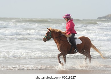 Lets paddle-horse and rider enjoy a trot at the sea edge on beach in Anglesey Wales.