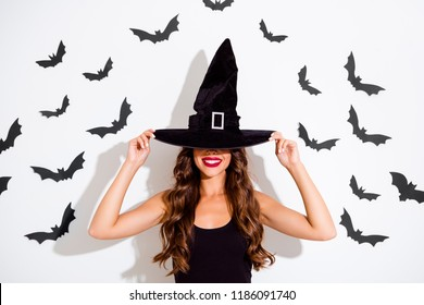 Let's play hide and seek? Close up portrait of attractive, careless, carefree, sorceress curly brunette lady covering her eyes with the cap make big toothy smile isolated on white background