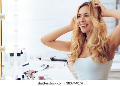 Lets play with my look! Side view of beautiful young woman looking at her reflection in mirrorand keeping hands in hair while sitting at the dressing table