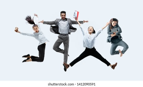 Let's start with aroma coffee. Happy office workers jumping and dancing in casual clothes or suit with drinks and folders isolated on studio background. Business, start-up, working open-space concept.