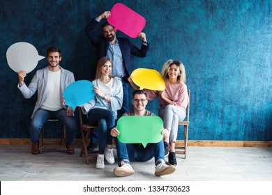 Let's start a conversation. We speak the language of success. Diverse group of businesspeople holding up speech bubbles while they wait in line