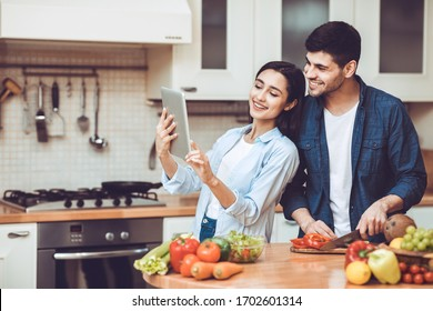 Let's Try This Recipe. Beautiful young couple using digital tablet and smiling, cooking together in kitchen at home