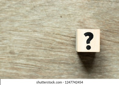 Letter block in question mark on wood background