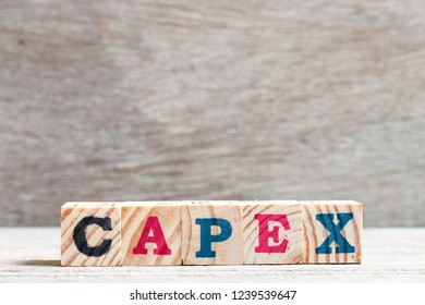 Letter block in word capex (abbreviation of capital expenditure) on wood background