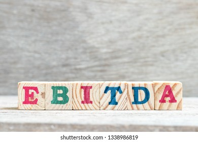 Letter block in word EBITDA (abbreviation of earnings before interest, taxes, depreciation and amortization) on wood background