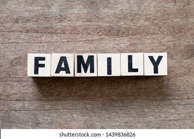 Letter block in word family on wood background