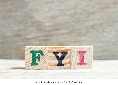 Letter block in word FYI (Abbreviation of For your information) on wood background