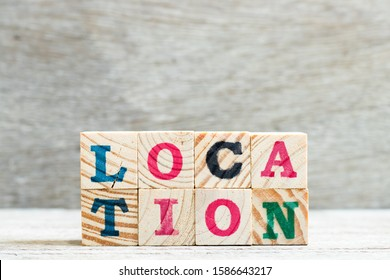 Letter block in word location on wood background