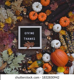 Letter board with phrase GIVING THANKS surrounded by pumpkins, gourds and autumn leaves