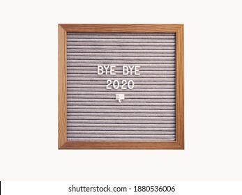 Letter board with words BYE BYE 2020 and nasty gesture. Result of year. Copy space on white background.
