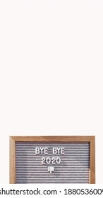 Letter board with words BYE BYE 2020 and nasty gesture. Result of year. Copy space on white background. Vertical banner 9:16.