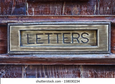 Letter box close-up, brushed copper and old painted wood