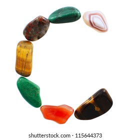 The letter C spelled with semi-precious stones against white background