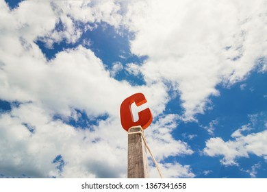 Letter C wood in front of blue cloud sky