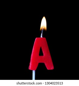 Letter A celebration birthday candle against a black background