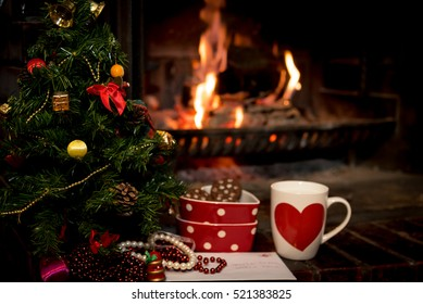 Letter, cookies and milk for Santa Claus below Christmas tree by fire place