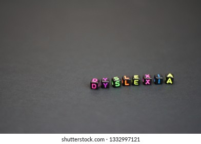Letter cubes of Dyslexia among other text cubes or dices. Selectively focused. Isolated on black surface.