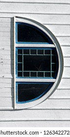 The letter D is formed by a tilted arched window on an old white barn.  Trim is painted with blue paint.