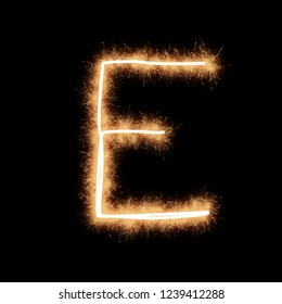 Letter E of alphabet written by squib sparks on a black background.