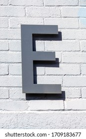 The letter E done in brushed steel on a brick wall