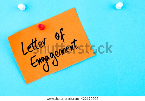 Letter Of Engagement written on orange paper note pinned on cork board with white thumbtack, copy space available