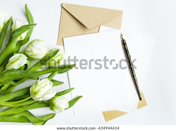 Letter, envelope and fresh bouquet on white background. Wedding invitation cards or love letter with white tulips. Romantic or holiday concept, top view, flat lay, overhead view