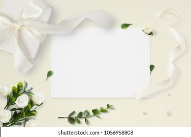 Letter, envelope and a present on pastel yellow background. Wedding invitation cards or love letter with chrysanthemums. Valentine's day or other holiday concept, top view, flat lay, overhead view