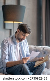 Letter, envelope. Serious young adult man carefully looking at a letter in his hands sitting on a sofa at home.