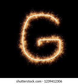 Letter G of alphabet written by squib sparks on a black background.