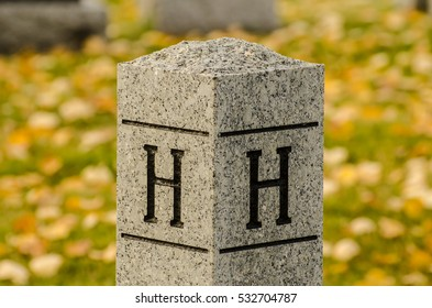 Letter H  carved into stone post