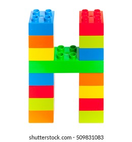 Letter H made from colorful plastic toy bricks isolated on white background