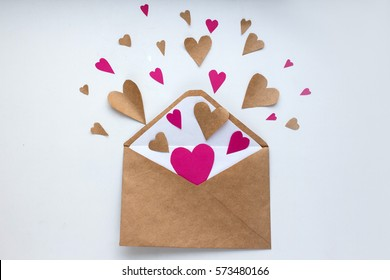 Letter with hearts Valentine day love letter. Envelope from craft paper with red hearts heap spread on white wood background. Lover's holiday confession or proposal concept