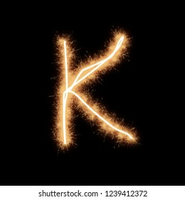 Letter K of alphabet written by squib sparks on a black background.
