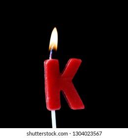 Letter K celebration birthday candle against a black background
