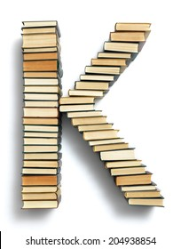 Letter K formed from the page ends of closed vintage hardcover books standing on a white background from a set or series of numbers