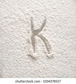Letter K written on flour