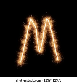 Letter M of alphabet written by squib sparks on a black background.