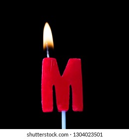 Letter M celebration birthday candle against a black background