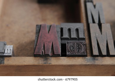 the letter M in different sizes and fonts in a wood type case, focus on the intricate, decorative metal M